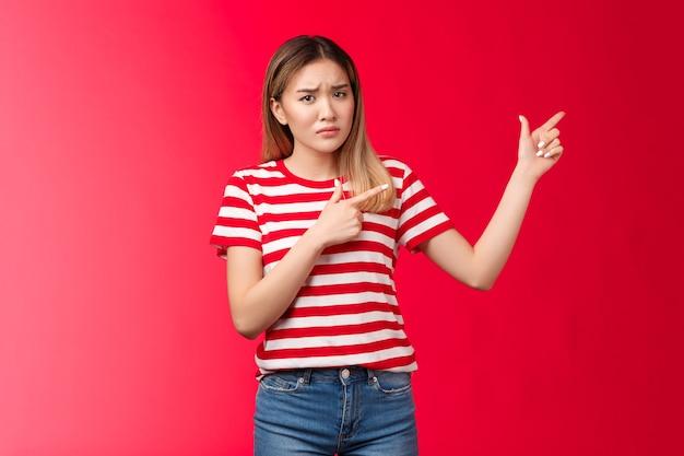 Fidanzata asiatica lunatica dispiaciuta che agisce in modo infantile immaturo indicando l'angolo in alto a destra sconvolto, accigliato dubbioso insoddisfatto, guarda la telecamera esitante e riluttante, sta in piedi indifferente sullo sfondo rosso.