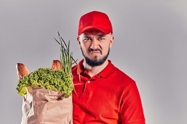 Corriere arrabbiato triste dispiaciuto in una maglietta rossa e un berretto tiene un sacchetto di cibo isolato su uno sfondo grigio. consegna cibo a domicilio.