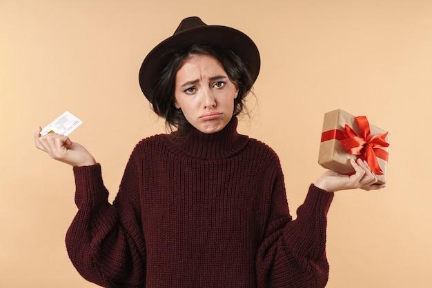 Dispiaciuto triste giovane donna bruna in posa isolato su muro beige muro in possesso di carta di credito e casella presente.