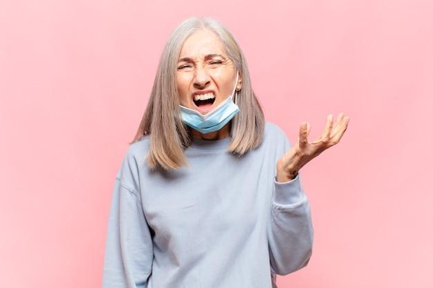 Donna graziosa senior dispiaciuta con mascherina chirurgica, pandemia covid