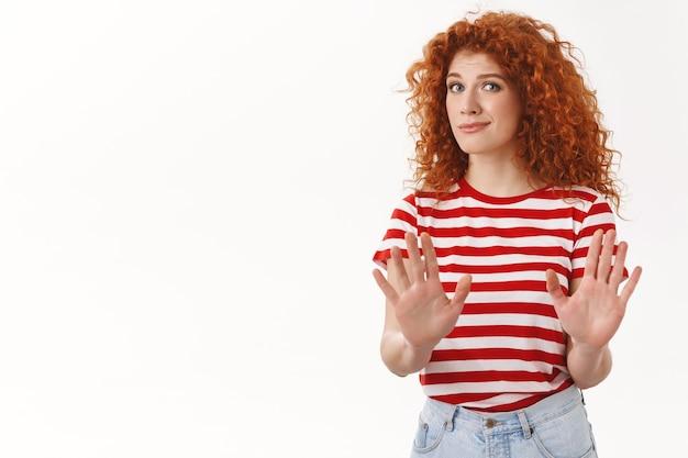 Fidanzata attraente rossa scomoda scontenta passa alza le mani ferma il gesto di rifiuto chiedendo abbastanza attesa fine relazione rifiutando offerta, muro bianco