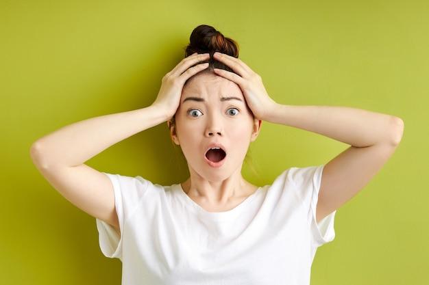 Scontento sconvolto femmina caucasica urlando e afferrando la sua testa isolata su sfondo verde, rimanere scioccato, sorpreso da qualcosa di incredibile