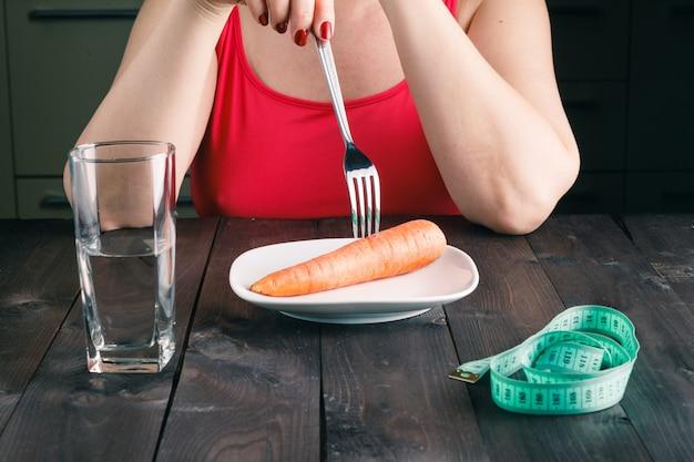 Donna dispiaciuta mantenendo una dieta rigorosa e mangiando verdure