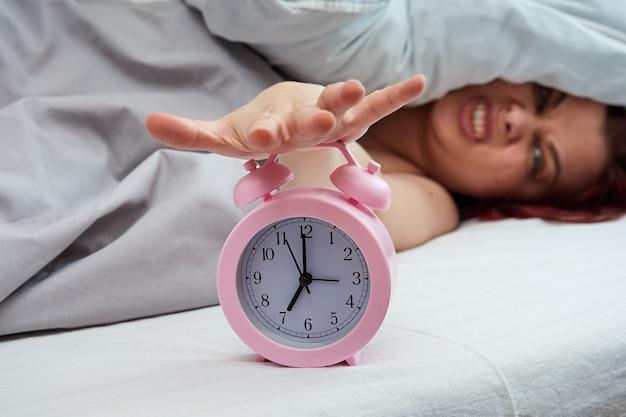 Donna dispiaciuta sdraiata a letto fermando la sveglia al mattino presto.