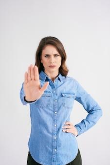 Donna dispiaciuta che mostra il segnale di stop
