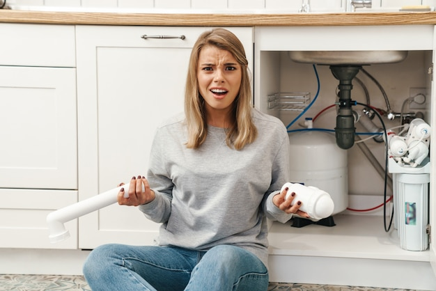 Dispiaciuta giovane donna bionda con tubi idraulici mentre è seduta sul pavimento vicino al lavello della cucina