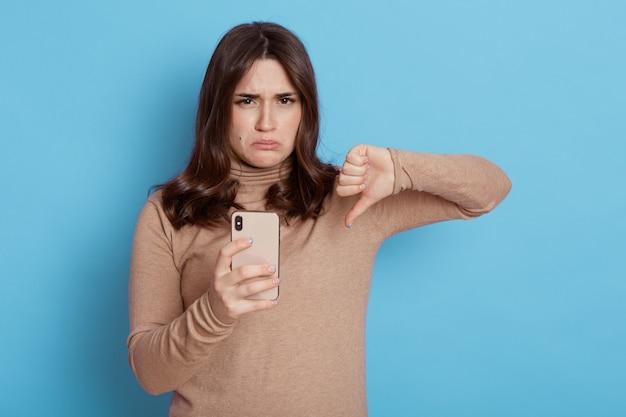 Dolcevita beige casual della giovane donna dai capelli castani scontenta tiene il telefono cellulare, mostrando il pollice verso il basso isolato sulla parete di colore blu, il viso accigliato e le labbra imbronciate.