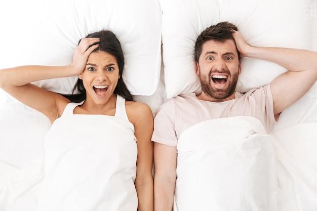 Una giovane coppia di innamorati dispiaciuta giace a letto sotto la coperta urlando