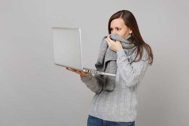 Giovane donna dispiaciuta in maglione grigio che copre la bocca con la sciarpa, lavorando su computer pc portatile isolato su sfondo grigio muro. stile di vita sano, consulenza sul trattamento online, concetto di stagione fredda.