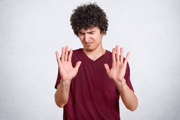 Il giovane dispiaciuto mostra il gesto di arresto, chiede di non disturbarlo, tiene i palmi davanti, non gli piace qualcosa, vestito con una maglietta casual