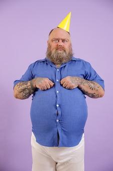 L'uomo scontento con sovrappeso in cappello da festa posa su sfondo viola