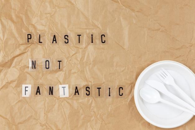 Elettrodomestici usa e getta piatto, forchetta, cucchiaio, coltello, frase con lettere su base trasparente plastica non fantastica su carta da lavoro sgualcita marrone