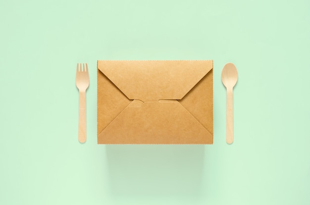 Scatola, forchetta e cucchiaio per alimenti in carta monouso e compostabili su sfondo verde per il concetto di giornata mondiale dell'ambiente