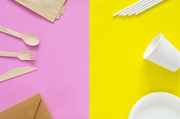 Confezioni monouso, compostabili e riciclabili su sfondo giallo e rosa