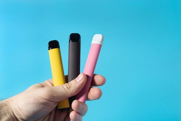 Sigarette elettroniche usa e getta in primo piano in mano sul blu con le ombre