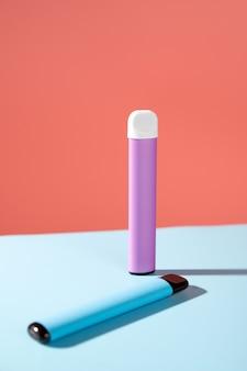 Sigarette elettroniche usa e getta con ombra su una parete rosa e blu con spazio per le copie il concetto di fumo moderno vaping e nicotina