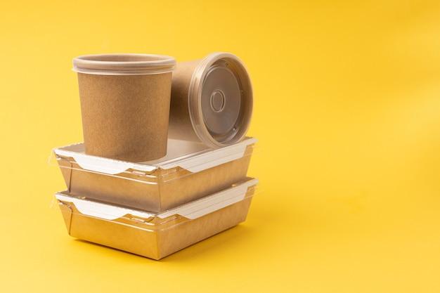 Scatole di consegna cibo usa e getta su sfondo giallo
