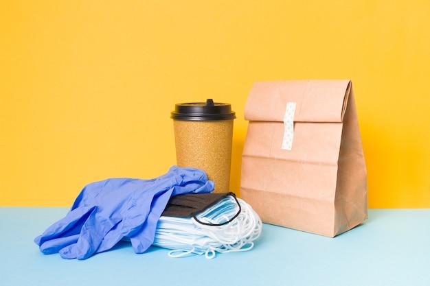 Guanti monouso, maschere per il viso e prodotti per la consegna, la consegna di cibo durante un'epidemia
