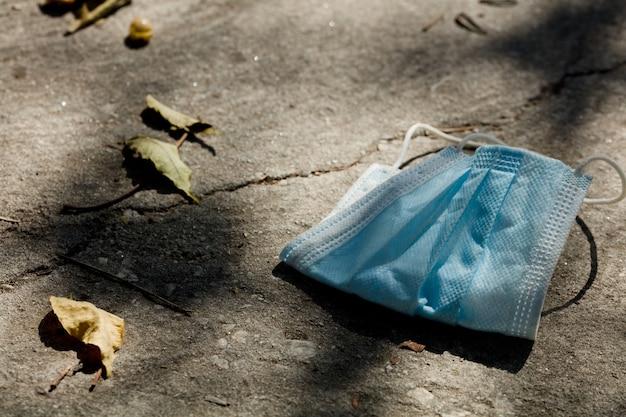 Maschera usa e getta sdraiato sulla strada. eliminare in modo errato la maschera per il viso usata