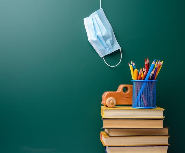 Maschera medica usa e getta, pila di libri e cancelleria scolastica sul bordo di gesso verde