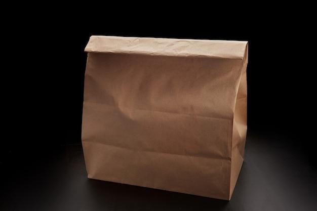 Sacchetto di carta usa e getta per la consegna del cibo, su sfondo nero con posto per il testo