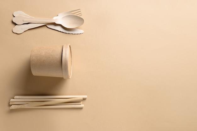 Bicchieri di carta usa e getta singoli cucchiai di legno forchette cannucce di bambù su beige