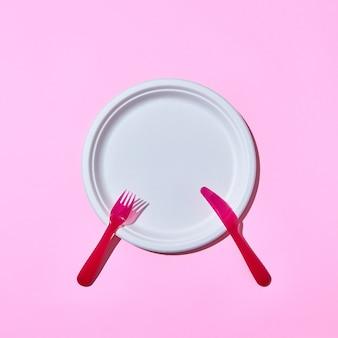 Set di posate in plastica usa e getta servito forchetta e coltello su uno sfondo rosa con spazio di copia.