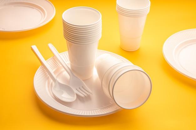 Stoviglie monouso in plastica. gruppo di piatti vuoti, tazze, cucchiai, forchette e utensili sul tavolo giallo
