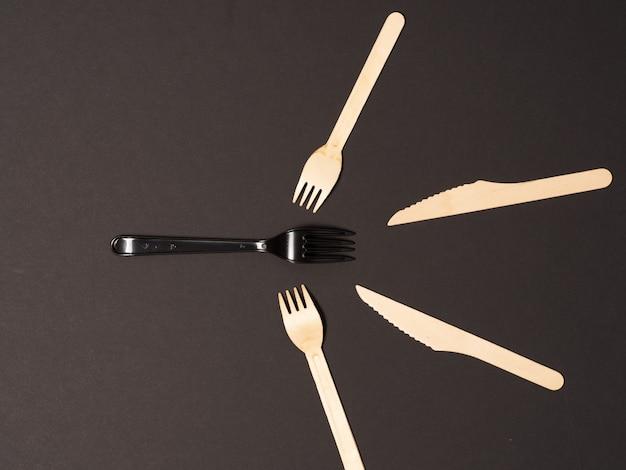 Forchetta di plastica usa e getta circondata da stoviglie in legno usa e getta ambientali su sfondo di carta nera. concetto non plastico
