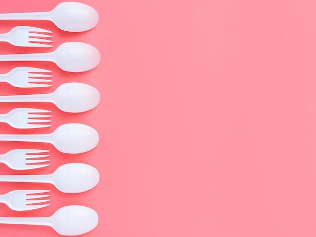 Forchette e cucchiai di plastica usa e getta si trovano in fila su uno sfondo rosa,