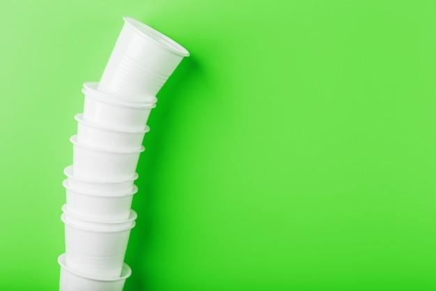 Stoviglie monouso in plastica su una superficie verde con spazio libero. vista dall'alto