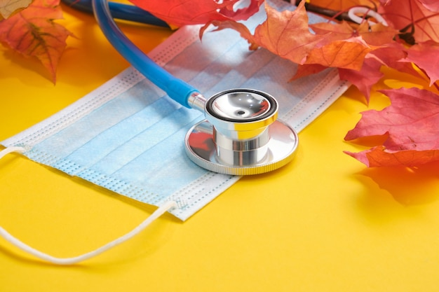 Maschera medica protettiva monouso e stetoscopio e foglie d'acero autunnali su sfondo giallo