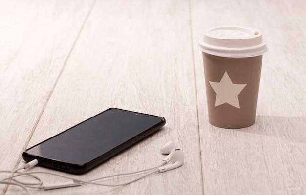 Tazza da tè usa e getta e riciclabile con telefono a stella con auricolari sul tavolo di legno