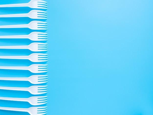Stoviglie usa e getta, forchette di plastica bianche isolate su uno sfondo blu con spazio di copia.