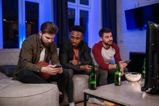 Insoddisfatto del gioco della squadra preferita, moderni compagni maschi multirazziali di bell'aspetto che bevono birra e navigano sui loro smartphone