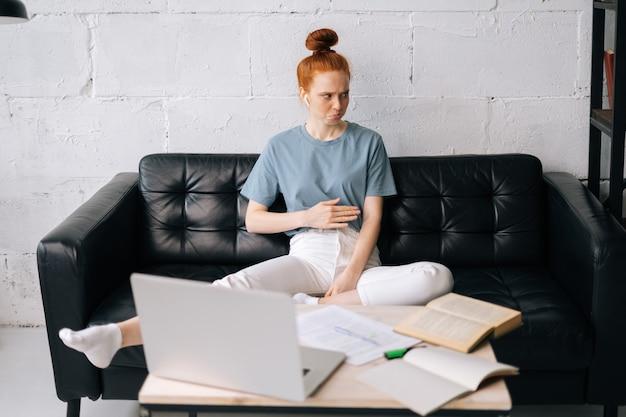 Giovane donna d'affari rossa insoddisfatta seduta alla scrivania con computer portatile e documenti cartacei