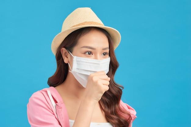La donna insoddisfatta con il cappello protegge il viso con la maschera, pensa al rischio di malattie epidemiche, ha un'infezione da virus