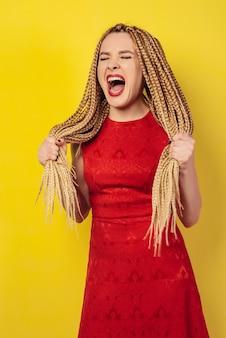 La donna insoddisfatta in vestito rosso grida tenendosi sulle sue trecce africane