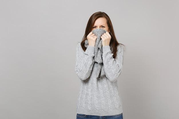 Giovane donna insoddisfatta in maglione grigio che copre la bocca con sciarpa isolata su sfondo grigio in studio. stile di vita sano persone emozioni sincere, concetto di stagione fredda. mock up copia spazio.