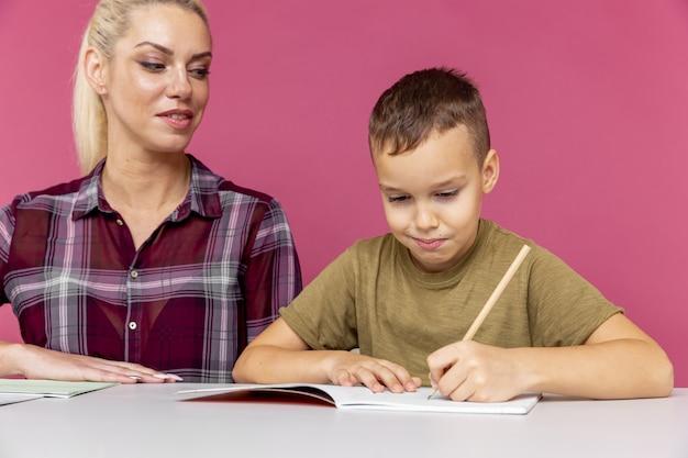 Compiti a distanza insieme. mamma con bambino che studia a casa.