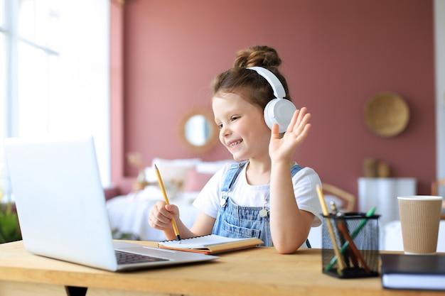 Insegnamento a distanza. bambina allegra in cuffia utilizzando il computer portatile che studia tramite il sistema di e-learning online.