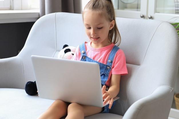Insegnamento a distanza. bambina allegra che utilizza il computer portatile che studia tramite il sistema di e-learning online.