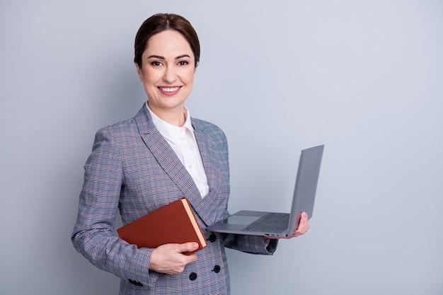 Concetto di apprendimento a distanza. foto ravvicinata di una donna istruita intelligente e sicura di sé che usa il netbook per dimostrare la presentazione agli studenti isolati su uno sfondo di colore grigio