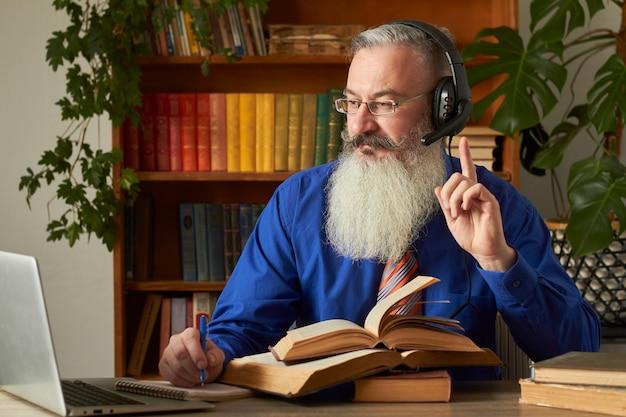 Concetto di apprendimento a distanza. insegnante professore tutor insegna disciplina online. l'uomo barbuto maturo risponde alla domanda dell'insegnante tramite il computer portatile.