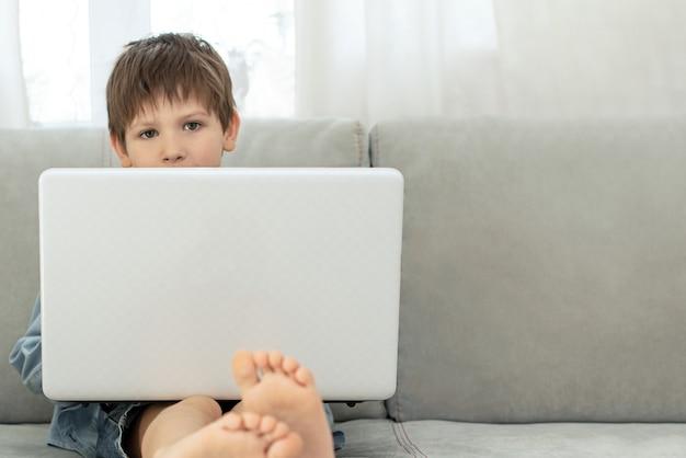 Apprendimento a distanza durante l'isolamento durante la quarantena nel coronovirus. ragazzo e laptop a casa. Foto Premium