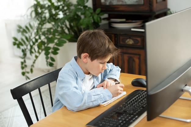 Apprendimento a distanza durante l'isolamento durante la quarantena nel coronovirus. ragazzo e laptop a casa.