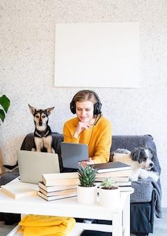 Insegnamento a distanza. e-learning. giovane donna sorridente in maglione giallo e cuffie nere studiando online utilizzando il laptop, seduto sul divano a casa