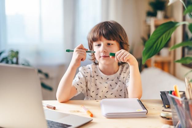 Formazione online a distanza. ragazzo caucasico del bambino di sorriso che studia a casa con il computer portatile e che fa i compiti della scuola. ubicazione del bambino di pensiero al tavolo con il taccuino. di nuovo a scuola.