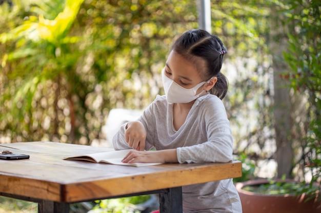 Formazione online a distanza. bambino con una maschera per guardare una lezione online.
