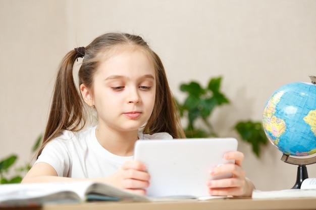 Formazione in linea di apprendimento a distanza. la ragazza della scuola fa i compiti sul tablet a casa. quarantena